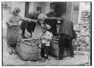 Armenian refugee women and child getting food relief.png