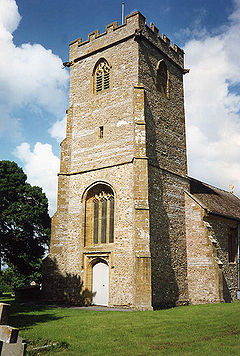 Stone two stage square tower with buttresses.