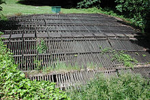 A horizontal wooden rack roughly 30 feet (9.1 m) wide and 30 feet (9.1 m) long lies in flat, grassy area.