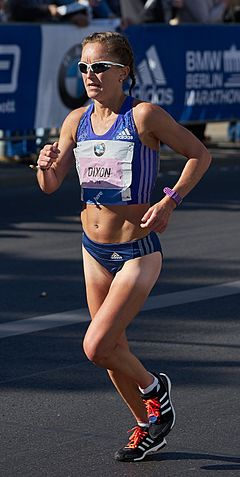 A woman wearing blue athletics running kit and sunglasses is running along a street. She has a competitor identifier 'Dixon' pinned on her chest, with the event sponsor's logo.