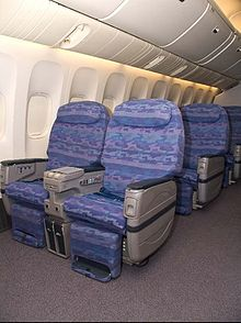 The interior of Biman's Boeing 777 aircraft showing the fronts of seats which are light blue in colour.