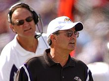 Candid photograph of Zauner standing in front of Brian Billick on a football sideline wearing a black polo shirt and white baseball cap both of which bear the Baltimore Ravens logo