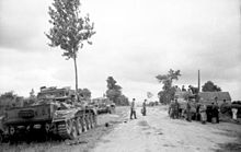Two tanks are parked on a grass verge to the left of a road while another tank is parked on the right side being inspected by a group of men. Two men are standing in the middle of the road.