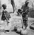 COLLECTIE TROPENMUSEUM Een Samo vrouw schenkt water vanuit een putaker in waterpotten TMnr 20010190.jpg