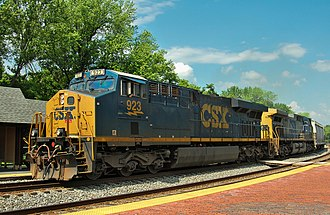 CSX Transportation - CSX locomotives lead a train eastbound. In the lead is an ES44AH, followed by an AC4400CW.