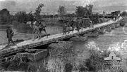 Camels being led across pontoon bridge