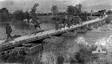 Camels being led across pontoon bridge
