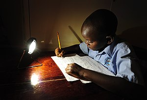 Christopher from Zambia studying by the light of a solar lamp.jpg