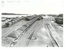 Loaded rail coal trucks, rail tracks and the river on the left