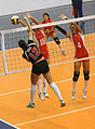 Coast Guard Lt. Catharine Lori Johann drives a spike past Chinese blockers during the U.S. women's first volleyball game at the Military World Games in Hyderabad.JPG