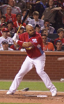 A right-handed batter is at the plate, looking toward the pitcher's mound. Wearing a red uniform and white pants, there is a crowd behind him with jerseys of various colors.