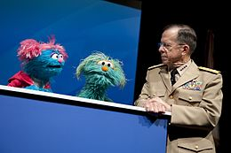 Defense.gov News Photo 100413-N-0696M-244 - Chairman of the Joint Chiefs of Staff Adm. Mike Mullen speaks with Sesame Street Muppets Jesse and Rosita at a preview of the PBS special When.jpg