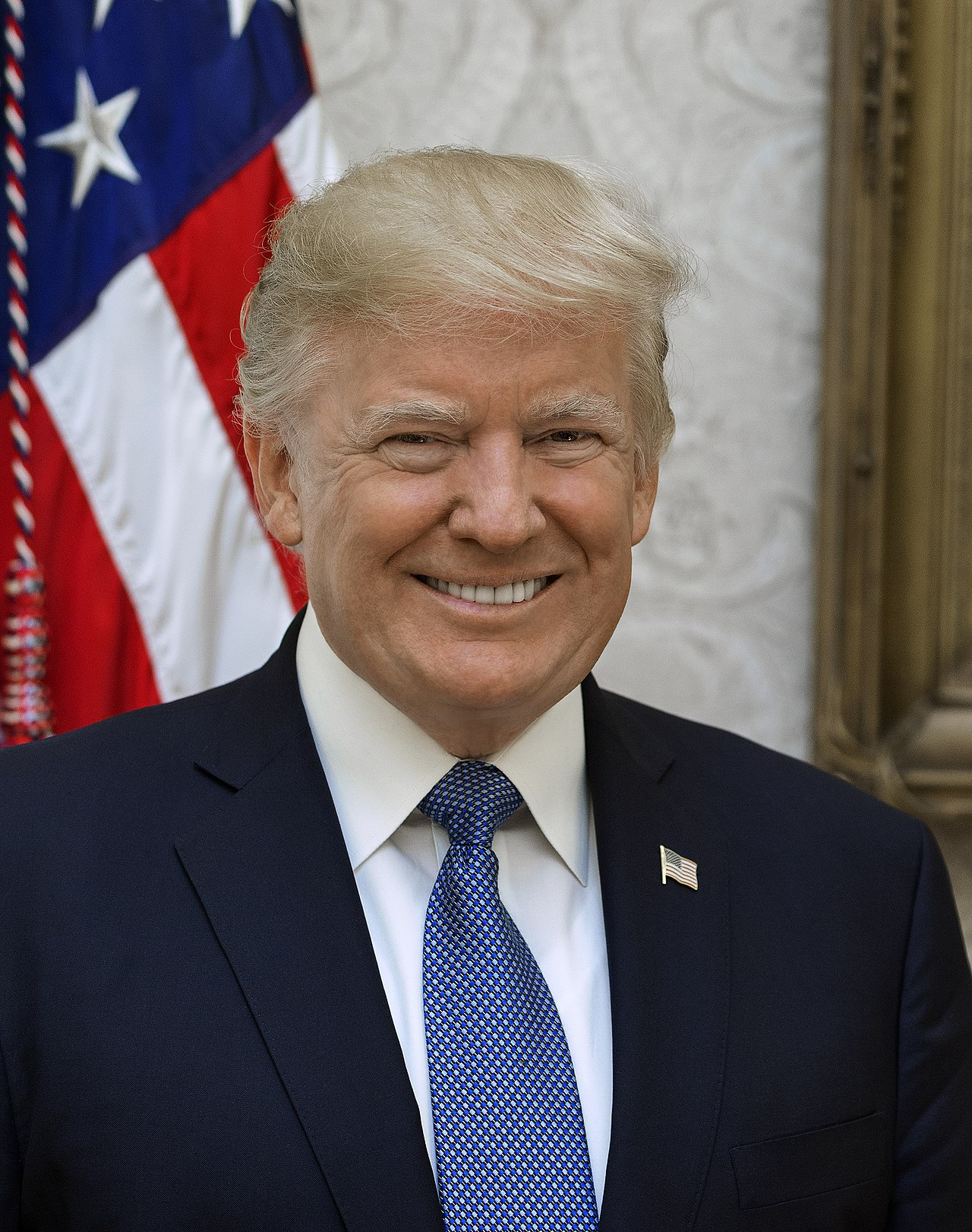 Official White House portrait. Head shot of Trump smiling in front of the U.S. flag, wearing a dark blue suit jacket with American flag lapel pin, white shirt, and light blue necktie.