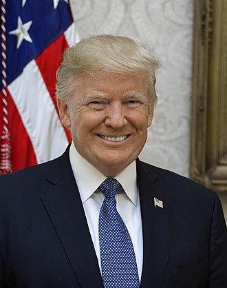 Head shot of Trump smiling in front of an American flag. He is wearing a dark blue suit jacket, white shirt, light blue necktie, and American flag lapel pin.