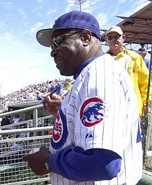 An older African American man wearing a white, pinstriped baseball uniform and sunglasses; he is autographing a baseball at a baseball game