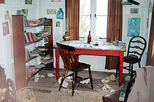 In the centre of a cluttered, whitewashed room stands a red table with two chairs, behind is a double window with simple brown curtains. Writing paraphernalia is strewn across the room