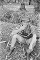 Een korporaal rookt een sigaret tijdens een pauze. Op zijn schoot ligt een Tomm…, Bestanddeelnr 482-3-3.jpg