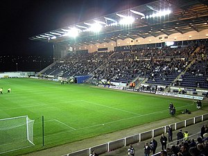 An evening game at a football stadium. The main stand on the right is filled with spectators and the empty pitch is being prepared for playing on the left
