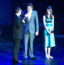 Three people on a stage, Johnston is being addressed by a man in a grey suit with a microphone. A teenage girl performer Faryl Smith, who has long brown hair and wears a green dress, is looking on.