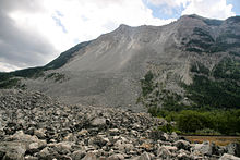 Side view of a mountain scarred by a large debris field down its side. A field of rock lies at its base.