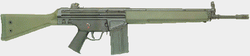 A green Heckler & Koch G3A3 battle rifle lain on a grey background, pointing to the viewer's right