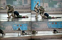 A four-picture series of photographs. Clockwise from the upper left: A Marine tries dragging a wounded Marine down a city street; a sailor runs over to help him; the rescuing Marine is shot; both Marines lie wounded on the street.