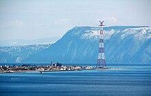 Foto scattata dallo stretto di Messina. In primo piano la punta estrema della Sicilia e, sullo sfondo, il monte Sant'Elia innevato con, sulla sinistra, il terrazzamento del centro abitato di Palmi