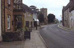 Street scene showing a pub the Ilchester Arms on the left with several other buildings leading to a church tower.