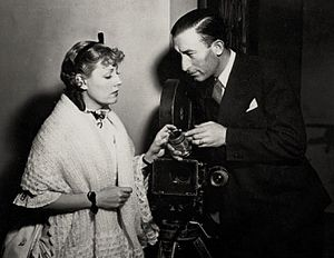 John J. Mescall - Actress Irene Dunne with cinematographer John J. Mescall on the set of Show Boat (Universal, 1936)