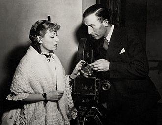 John J. Mescall - Actress Irene Dunne with cinematographer John J. Mescall on the set of Show Boat (Universal, 1936)