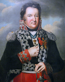 Painting shows a chubby man with his right hand thrust into his coat and his left hand on his sword hilt. He wears a dark blue military uniform with red cuffs and red breeches and silver frogging.