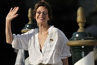 Woman with short, dark hair in a white blouse, smiling and waving
