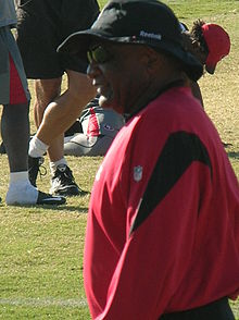 Candid waist-up photograph of Raye from the side standing on a football field, wearing a red and black pullover, a wide-brimmed hat bearing a Reebok logo and sunglasses