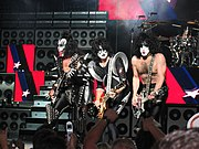 The band Kiss is shown onstage at a concert. From left to right are the bassist Gene Simmons, two electric guitarists and the drummer, who is at the rear of the stage. Simmons is wearing spiked clothing and his tongue is extended. All members have white and black face makeup. Large guitar speaker stacks are shown behind the band.