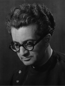 A middle-aged man in a jacket. He is looking down, slightly turned to his right