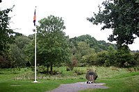 A clearing sparsely surrounded by trees and bushes. A gravel-lined spot is at the centre, sporting a stone with flowers lain in front of it. On the left stands a flagpole, whose flag lies unfurled.