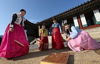 Korean New Year - People wearing hanbok and playing yut.