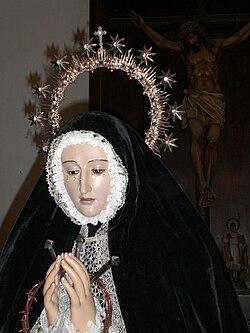 Nuestra Señora de la Soledad, espera en la Sacristia antes de ser depositada sobre su Trono. Tras Ella la Imagen de su Hijo Crucificado