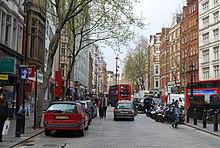 Une rue pavée bordée d'immeubles anciens rouges et blancs. Parmi la circulation routière se trouvent deux bus rouges à étage.