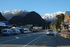 Main street of Franz Josef in the morning with snow-covered Baird Range and Fritz Range in the background.jpg