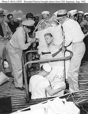 USS Argonaut (SM-1) - A Marine Raider, injured during the Makin operation, is lifted through a hatch on USS Argonaut to be taken ashore at Pearl Harbor, 26 August 1942.