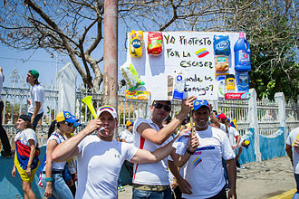 "Shortages in Venezuela - A protester during the 2014 Venezuelan protests holding a sign saying, ""Yo protesto por la escasez. Donde los consigo?"" (I protest for the scarcity. Where can I get these?)."
