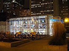 Rows of outdoor bike racks in a plaza in front of an interior-illuminated glass building at night
