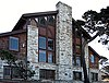 Photograph of Merrill Hall at the Asilomar Conference Grounds, a tall and broad peaked building of wood and stone.