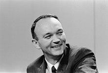Photographie en noir et blanc de Collins lors d'une conférence de presse.