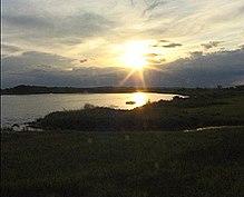 Słońce nisko nad horyzontem nad zbiornikiem wodnym otoczonym ciemną roślinnością