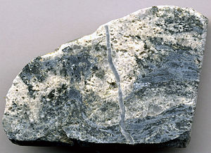 Climax mine - Molybdenum ore, Climax mine (5.3 cm across at its base). Molybdenite-quartz veins in alkaline granite. Dark silvery gray = molybdenite (MoS2).. Medium gray = quartz. Light colored areas = alkaline granite.