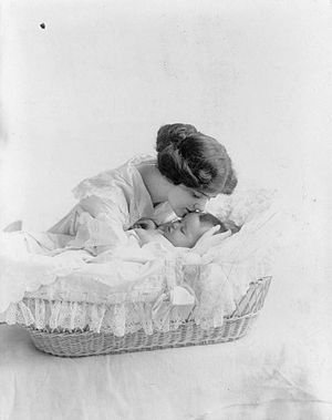 Young woman kissing baby in bassinet
