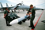 Munitions crewmen prepare a missile for loading onto an F-15 Eagle aircraft during the air-to-air combat training Exercise William Tell '82 DF-ST-83-11472.jpg