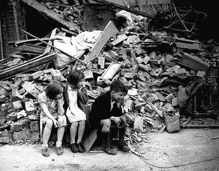 """Children in the east end of London, made homeless by the random bombs of the Nazi night raiders, waiting outside the wreckage of what was their home"". September 1940 (National Archives) NA-306-NT-3163V.jpg"